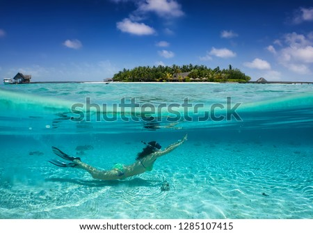 Woman in bikini snorkeling under turquoise, tropical water in the Maldives; split picture under and over water
