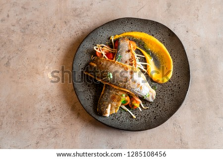Baked sea bass on a black plate, grey background #1285108456