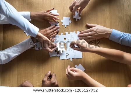 Above top view to the hands of diverse people assembling connecting jigsaw puzzle associates put pieces searching common solutions making right decisions together. Support and help in business concept #1285127932