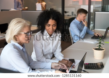 Middle aged experienced businesswoman company ceo helping to new employee afro millennial female with online task or corporate application useful program, fruitful teamwork of diverse workers concept Royalty-Free Stock Photo #1285131160