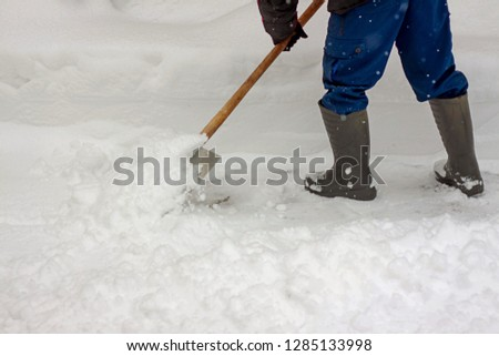 A man removes snow shovel after a snow storm in the winter. #1285133998