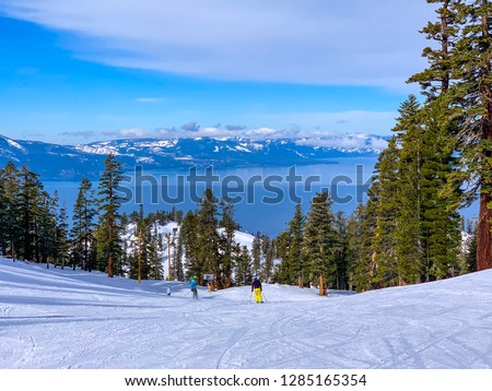 Heavenly Ski Resort, California, USA. Beautiful mountain covered with snow and a view of the blue Tahoe Lake. People skiing in the distance. #1285165354
