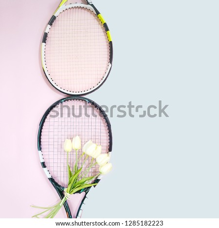 International Women's Day March 8 shape made of tennis rackets with bouquet white tulips and copy space on pastel pink and blue background. Valentine's day concept with tennis play. Flat lay. #1285182223