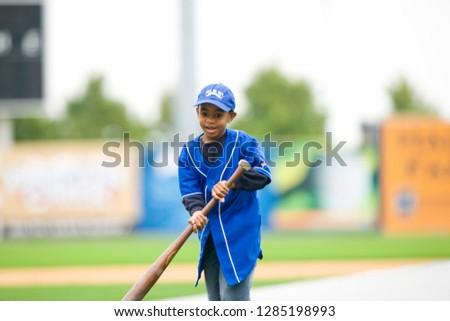 Young boy swinging a baseball bat on a playing field.