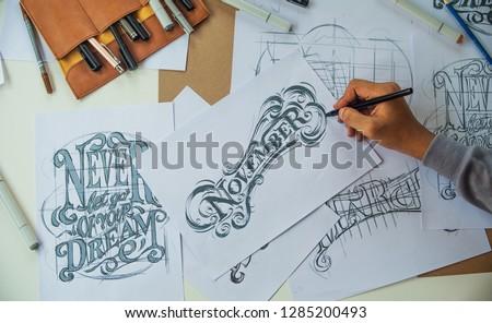 Typography Calligraphy artist designer drawing sketch writes letting spelled pen brush ink paper table artwork.Workplace design studio. #1285200493