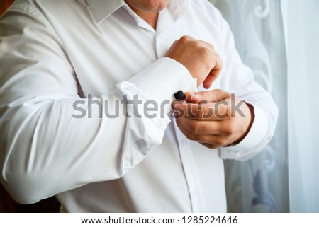 A man fastens expensive high-quality cufflinks on the sleeves of his shirt #1285224646