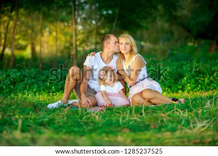 happy family in the evening park, sit on the grass and hug #1285237525