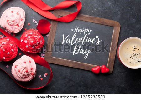 Valentine's day greeting card with delicious sweet cupcakes and coffee cup on stone background. Top view #1285238539