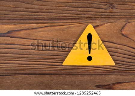 Exclamation mark on a yellow triangle background on a wood texture, copy space for design or text. Signs and symbols, Attention, danger, pay attention. #1285252465