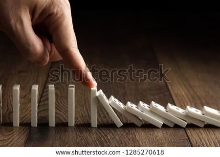 Creative background, Men's hand stopped domino effect, on a brown wooden background. Concept of domino effect, chain reaction, risk management, copy space. #1285270618