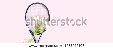 tennis love layout on pastel pink background with tennis racket with bouquet white tulips flowers. Women's Day March 8. Copy space. Valentine's day concept with tennis play. Flat lay, horizontal. #1285292107