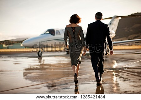 Well-dressed couple walking towards a private jet
