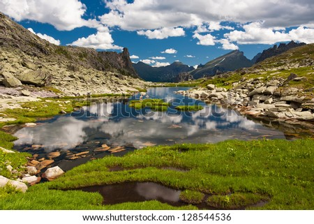 Clear lake between high mountains in summertime #128544536