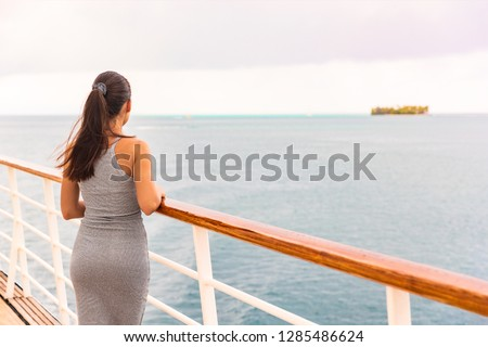 Luxury cruise ship vacation on tropical ocean travel - Young tourist woman watching sunset on deck of cruising boat. Tahiti destination, island in background.