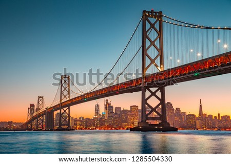 Classic panoramic view of San Francisco skyline with famous Oakland Bay Bridge illuminated in beautiful golden evening light at sunset in summer, San Francisco Bay Area, California, USA #1285504330