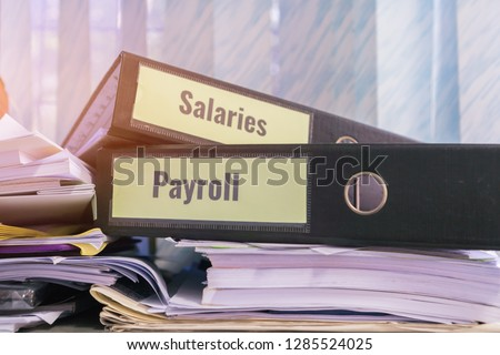 Payroll and salaries folders stack with label on black binder on paperwork documents summary report, HR-human resources business and bookkeeping accountancy concept in busy offices #1285524025