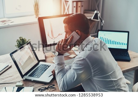 Trying to help someone. Young businessman in formalwear talking on the phone and analyzing data using computer while sitting in the office #1285538953
