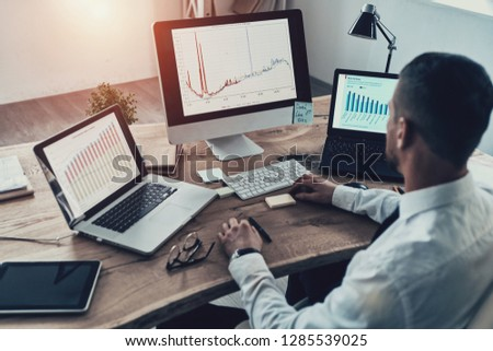 Analyzing sales pitch. Top view of young businessman in formalwear analyzing data using computer while sitting in the office #1285539025