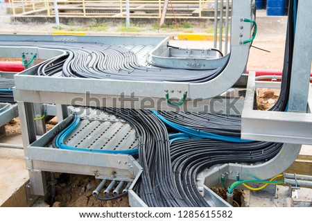 Power cables and instrument cables in the trays .Electric cables lying in metal cable trays.Cable tray and Cable ladder on Pipe Rack. #1285615582