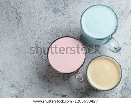 Trendy drinks: Blue, yellow and pink latte. Top view of hot butterfly pea or blue spirulina latte, yellow or gold turmeric latte and pink beetroot latte on gray cement background. Copy space for text #1285630429
