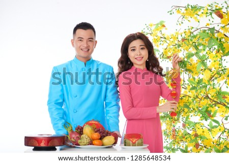Asian young couple preparing fruits and decorations for Lunar New Year celebration #1285648534