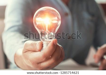 hand holding light bulb energy power concept #1285714621