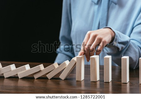 partial view of woman sitting at desk and preventing wooden blocks from falling isolated on black #1285722001