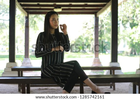 Elegant lady sitting alone on the wooden bench. #1285742161