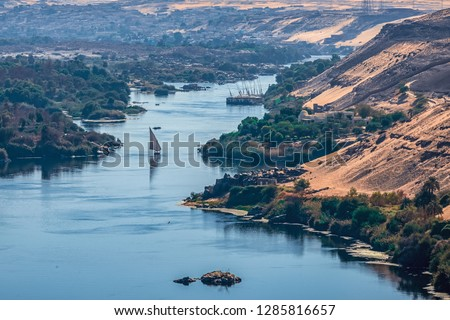 Sunset over the Nile River in the city of Aswan with sandy and deserted shores #1285816657