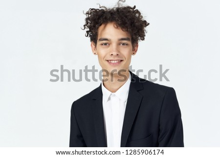 Cheerful handsome man in a dark suit with curly hair #1285906174