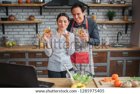 Cheerful couple stand together in kitchen. They hold glasses of wine and look on laptop. People smile. They have vegetables on table. #1285975405