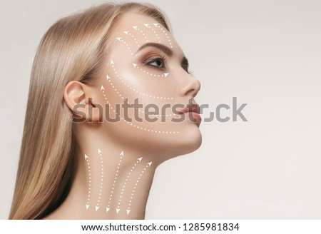 Close-up portrait of young, beautiful and healthy woman with arrows on her face. The spa, surgery, face lifting and skin care concept #1285981834
