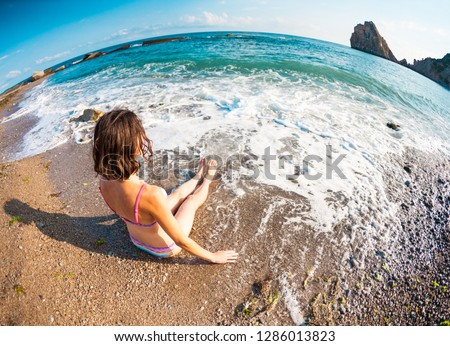 The girl sits on the beach. Woman bathes in the ocean. Rest on the coast. Slender brunette in a swimsuit sitting on the beach.