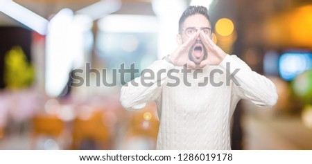 Young handsome man wearing glasses over isolated background Shouting angry out loud with hands over mouth #1286019178