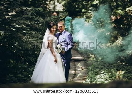UKRAINE, UZIN  - AUGUST 11, 2018:  wedding photo of a beautiful couple on the background of smoke bombs. Selective focus #1286033515