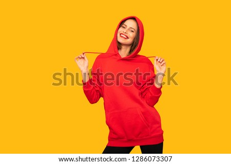 cool young woman posing with a red hoodie, hipster woman on yellow background #1286073307