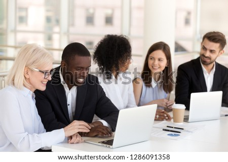 Diverse colleagues different race age businesspeople sitting together at desk in boardroom talking having pleasant informal conversation. Teamwork friendship at work between multiracial people concept #1286091358