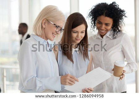 Happy middle aged business lady female director showing to multiracial worker women documents about cash monetary bonus for all employees for a job well done or project completion, good news concept #1286094958