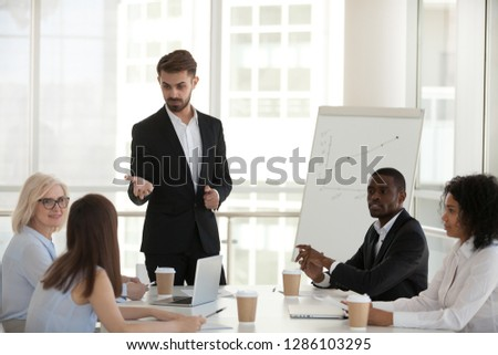 Confident coach communicating with international company staff pointing on caucasian worker female asking question. Diverse professional team members sitting in boardroom during seminar listens mentor #1286103295