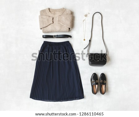 Blue midi pleated skirt, beige knitted sweater, small black cross body bag, belt, loafers (flat shoes) on grey background. Overhead view of women's casual day outfit. Flat lay, top view. Women clothes #1286110465