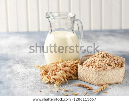 The concept of a vegetarian diet. Oat milk in the jug and oat and oat ears. Light background #1286113657