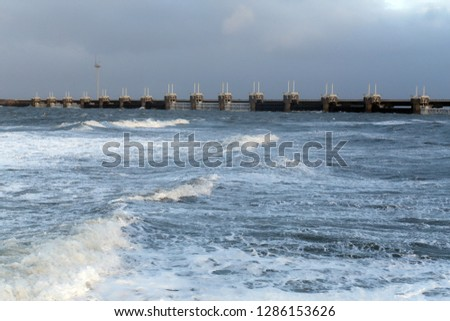 Storm surge barrier to protect against flood and storm with big waves in front #1286153626