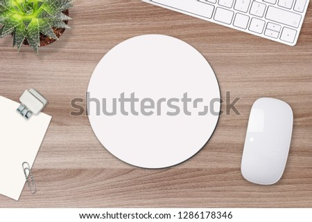 Mouse pad mockup. Round white mat on the table with props, mouse and keyboard #1286178346