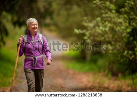 Happy mature woman enjoys a peaceful hike through the woods. #1286218858