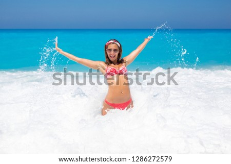 Beautiful young woman havin fun in the ocean splashing around and smiling daytime