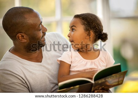 Happy father and daughter reading a book together.