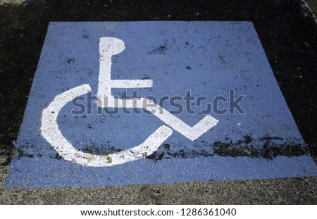 Parking for the disabled on the road, symbol and background #1286361040
