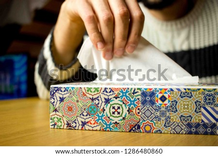 Hand taking a tissue from a tissues box. Concept of illness and cold. When the flu is coming Royalty-Free Stock Photo #1286480860