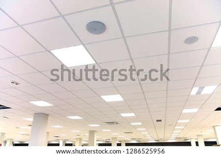 Modern design white office ceiling with white tiles and lighting #1286525956