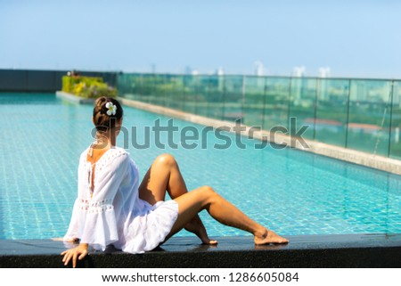 Young Woman relaxing by the side of the infinity pool  #1286605084